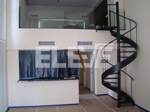 escalera caracol interior minimalista con cinta helicoidal baranda de vidrio laminado